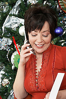 Senior woman using cell phone in front of Christmas tree