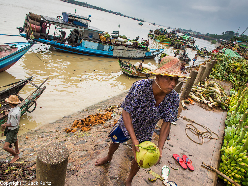 """10 JUNE 2014 - YANGON, MYANMAR:   Porters unload coconuts from a riverboat on the banana jetty. They unload the coconuts by throwing each coconut from the boat to a waiting truck on the shore. The """"banana jetty"""" is on the Yangon River north of central Yangon on Strand Road. Bananas, coconuts and other fruit are brought in here from upcountry, sold and reshipped to other parts of Myanmar (Burma). All of the labor here is done by hand. Porters carry the produce to the jetty and porters load the boats before they steam upriver.   PHOTO BY JACK KURTZ"""