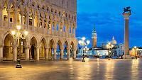 Der Dogenpalast und die Säule mit dem Markuslöwen auf dem Markusplatz in Venedig bei Nacht.