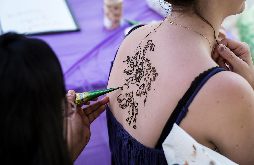 Bhakti Shah, left, puts the finishing touches on henna tattoo during the International Street Fair on Saturday, April 18, 2015.