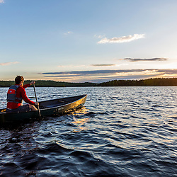 A man paddles his canoe on Long Pond at sunrise in Maine's north woods. Near Greenville, Maine.