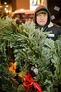 A vendor of Christmas greens braves the evening cold in the greenmarket in Union Square.