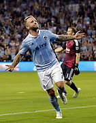 As Portland Timbers goalkeeper Jeff Attinella (1) stands in the background, Sporting Kansas City forward Johnny Russell (7) celebrates scoring a goal during the second half of a MLS soccer match in Kansas City, Kan., Saturday, Aug. 18, 2018. Sporting KC beat the Timbers 3-0.  (AP Photo/Colin E. Braley)