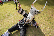 28 JUNE 2014 - DAN SAI, LOEI, THAILAND:  A drunk person in a ghost costume falls to the ground at Wat Ponchai in Dan Sai during the Ghost Festival. Phi Ta Khon (also spelled Pee Ta Khon) is the Ghost Festival. Over three days, the town's residents invite protection from Phra U-pakut, the spirit that lives in the Mun River, which runs through Dan Sai. People in the town and surrounding villages wear costumes made of patchwork and ornate masks and are thought be ghosts who were awoken from the dead when Vessantra Jataka (one of the Buddhas) came out of the forest.   PHOTO BY JACK KURTZ