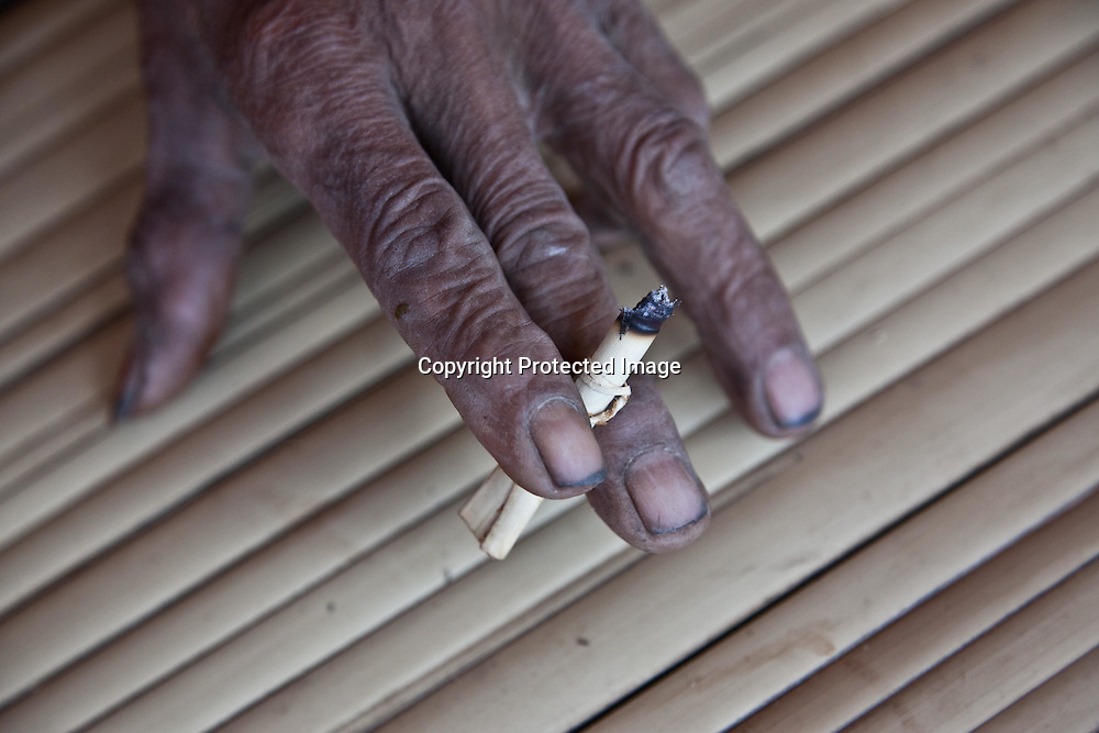 INDONESIA, Flores Archipelago, Ngada country, Tolela traditional village, old man smoking with hand made cigarette