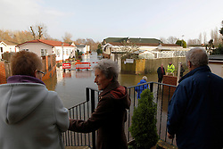 © Licensed to London News Pictures. 06/01/2014, Christchurch, UK. Residents watch their street flooded by the overflow River Stour at Iford Bridge, Christchurch, England , Monday, Jan. 6, 2014. Part of UK continue to be affected by floods and strong wind. Photo credit : Sang Tan/LNP