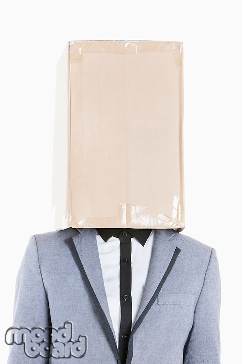 Young boy wearing jacket with box covered over his face on gray background