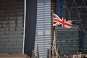 Seen from the south bank of the river Thames, a Union Jack flag flies on the bow of WW2 battleship HMS Belfast with the City of London - the capital's financial centre (aka The Square Mile) in the background, on 27th September 2018, in London, England.