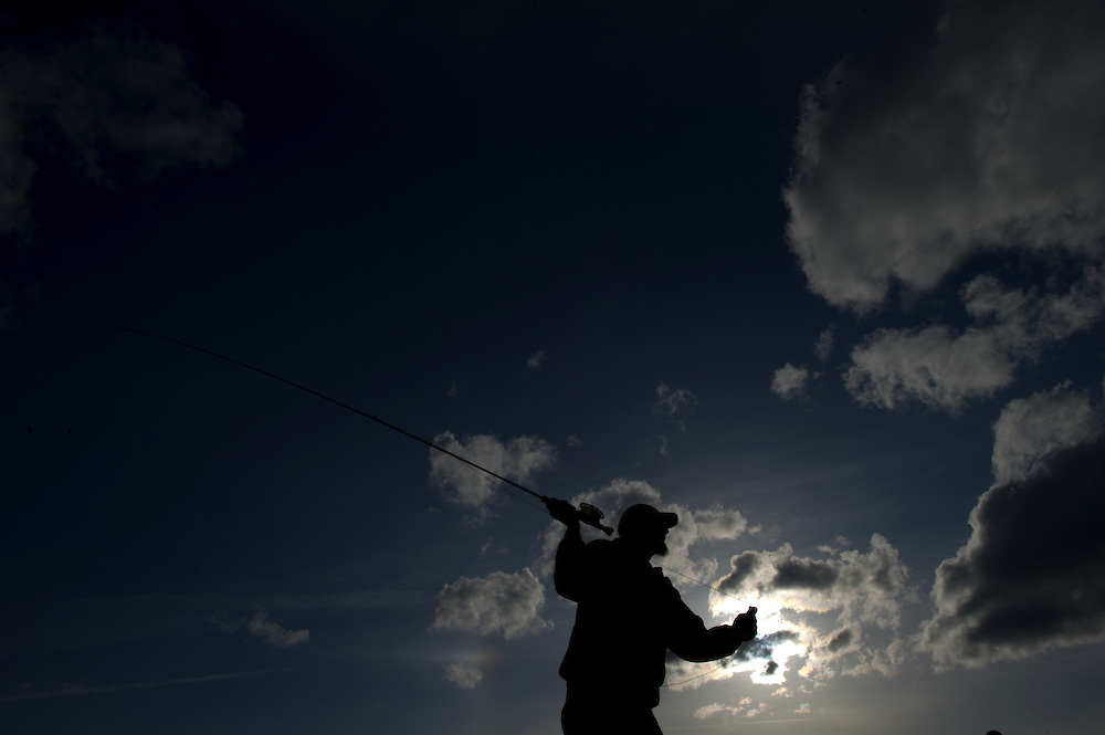 A fly fisherman takes a cast as the sun begins to set.