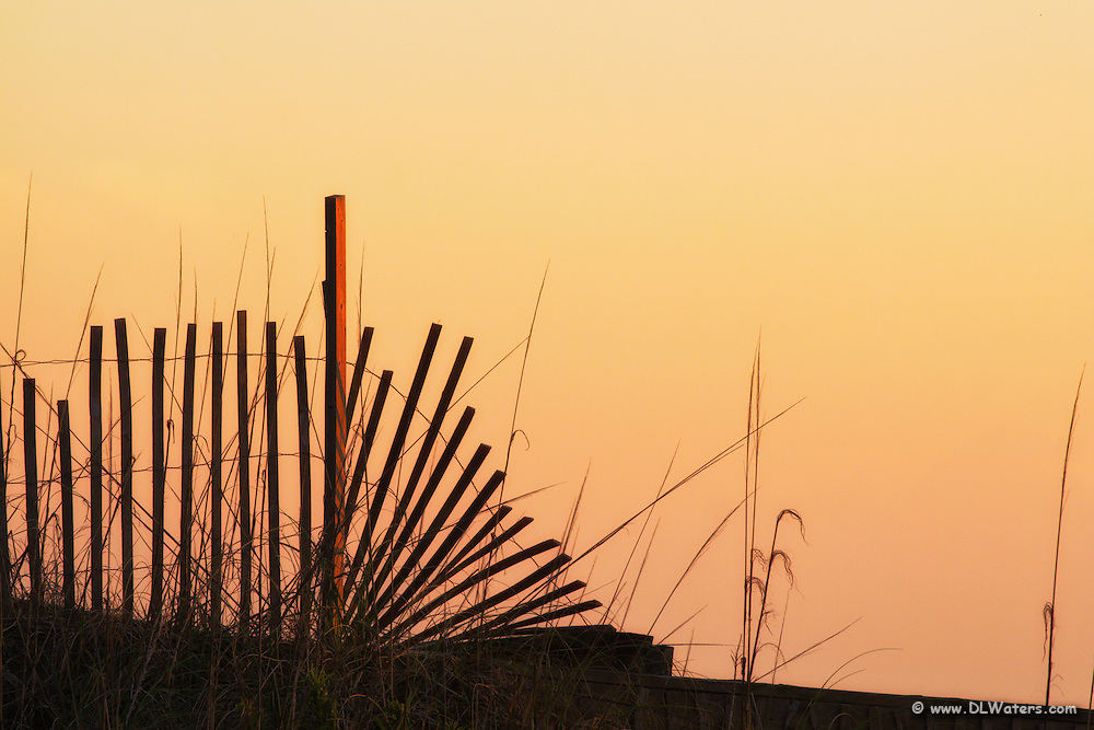 Sand fence silhouette at sunrise leaves a warm glow in the sky.