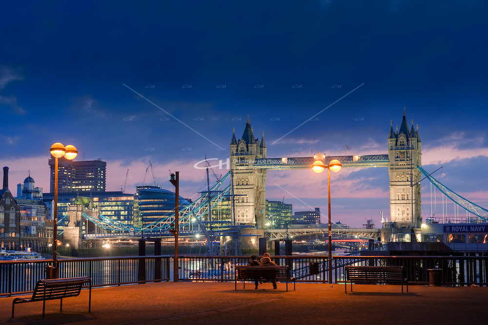 two people sit near tower bridge as night falls in london england uk