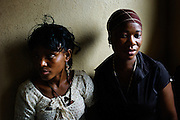Monrovian journalists Hawa Lumeh (left) and Edwina Sieh(right) of Monrovia's Ministry of Information and Tourism wait for a press conference to begin after the discovery of a cache of arms near the Liberia-Cote d'Ivoire border.