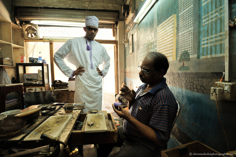 An indian silver smith estimates the value of a ring at his shop in the Nizwa Souk, Oman, 2011