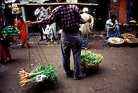 A Newari man carries his vegetables in the traditional way through the streets of Kathmandu.
