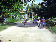 People cycling and walking along a main road on the island of La Digue, Seychelles