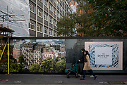 "A young family walks past a construction hoarding for the new luxury apartment development called The Denizen, a controversial unaffordable 10-storey building by Taylor Wimpey that locals say will dominate their view and block their daylight, on 30th October 2017, in London, England. Residents from Bowater House on the Golden Lane Estate have erected banners by artists Jeremy Deller and Elizabeth Price to picket the developers. Despite this, Wimpey say, ""We are one of the UK's largest residential developers. As a responsible developer we are committed to working with local people and communities."""