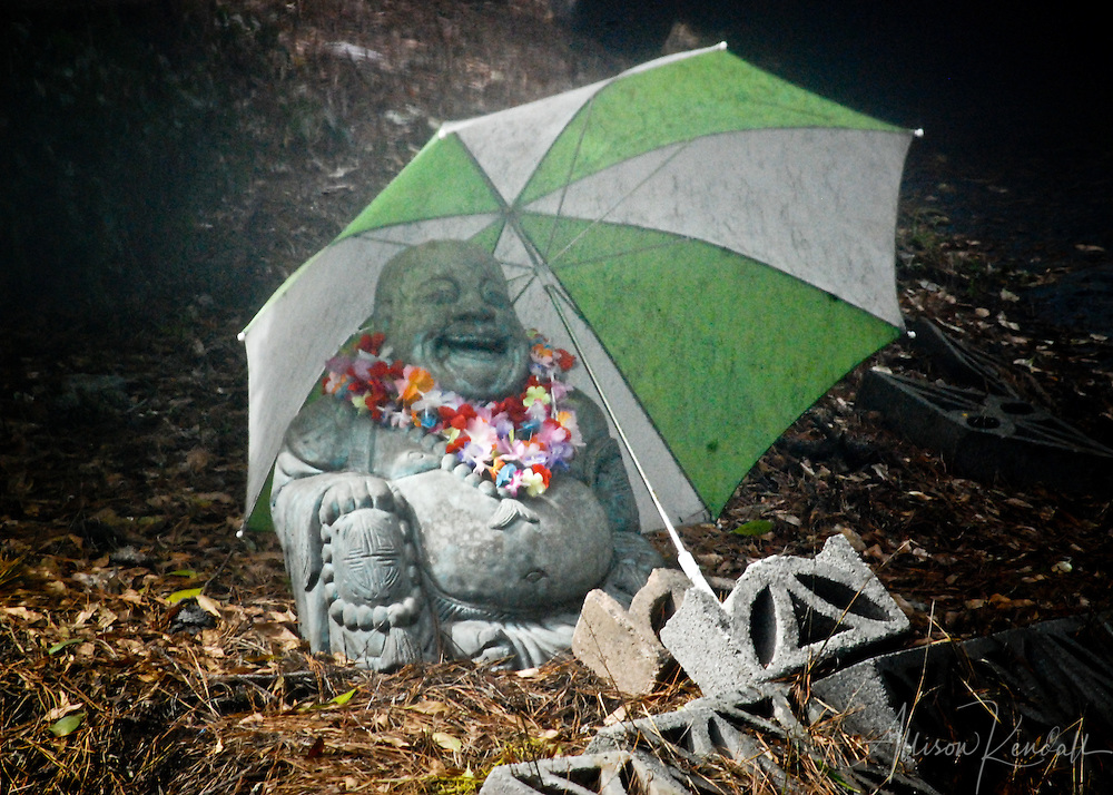 A laughing Buddha statue sits in the rain, beneath a green and white umbrella and adorned with a colorful lei, in Carmel-by-the-Sea, California