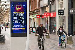 Glasgow, Scotland, UK. 1 April, 2020. Effects of Coronavirus lockdown on streets of Glasgow, Scotland. Cyclists ride past video screen with coronavirus health advice on Sauchiehall Street. Iain Masterton/Alamy Live News