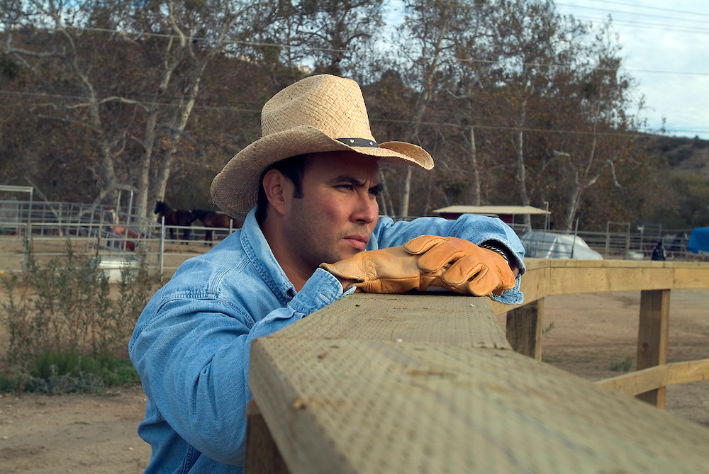 Lifestyle portrait of rancher watching his horses in a corral in San Diego, CA.