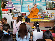 11 JULY 2014 - BANGKOK, THAILAND: A monk blesses people at Wat Mahabut for Asalha Puja Day. Asalha Puja is the day the Lord Buddha preached his first sermon to followers after attaining enlightenment. The day is usually celebrated by merit making and listening to a monks' sermons. It is also day before the start of the Rains Retreat, the three month period when monks stay in their temple for intense mediation and spiritual renewal.    PHOTO BY JACK KURTZ