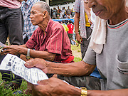 03 NOVEMBER 2012 - HAT YAI, SONGKHLA, THAILAND:  Spectators check the roster before placing bets at the bullfighting arena in Hat Yai, Songkhla, Thailand. Bullfighting is a popular past time in southern Thailand. Hat Yai is the center of Thailand's bullfighting culture. In Thai bullfights, two bulls are placed in an arena and they fight, usually by head butting each other until one runs away or time is called. Huge amounts of mony are wagered on Thai bullfights - sometimes as much as 2,000,000 Thai Baht ($65,000 US).      PHOTO BY JACK KURTZ