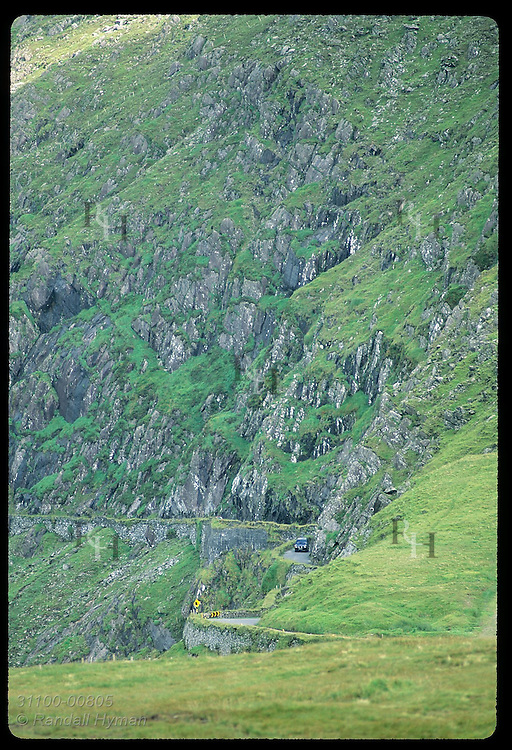 Dwarfed by rock cliffs, a car climbs narrow road up Conor Pass, Ireland's highest (1500');Dingle Ireland