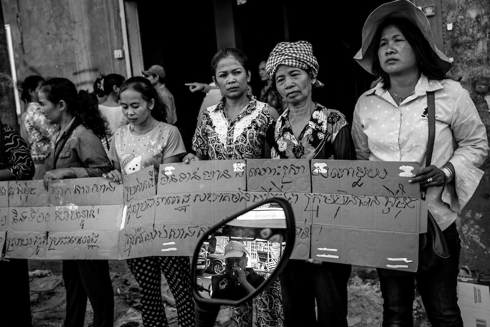 Land rights activits stage a protest in front of Borei Keila. The community of Borei Keila in Phnom Penh was once home to hundreds of families before land developer Phanimex bought the property rights to the area and forcefully evicted the residents who refused to accept their compensation package. Those who remained were forced to squat in the remains of the buildings, living in slum-like conditions and without access to plumbing or public electiricity.