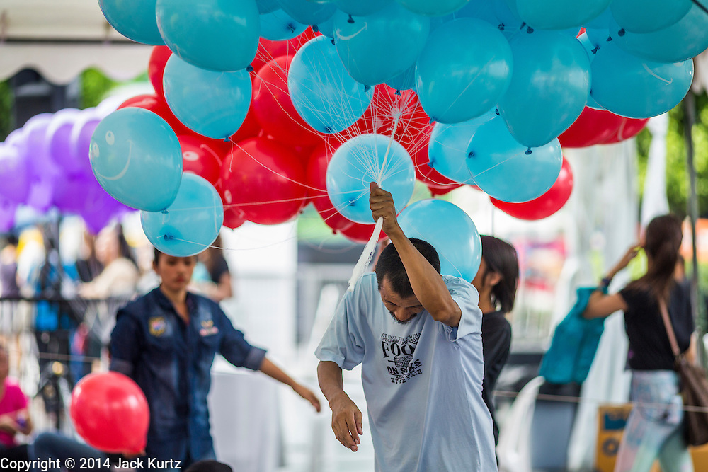 25 JULY 2014 - BANGKOK, THAILAND:  A man carries helium balloons through a crowd at the party restore happiness to the people at Ratchaprasong Intersection. The party was organized and sponsored by the Tourism Authority of Thailand and was promoted as an effort to restart Thailand's tourism industry, which has seen a significant drop in foreign arrivals since political violence started in 2013. There has been no violence since the coup on May 22, 2014, but tourism has not completely rebounded.    PHOTO BY JACK KURTZ