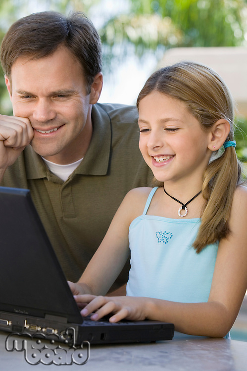 Father Watching Daughter Use Laptop