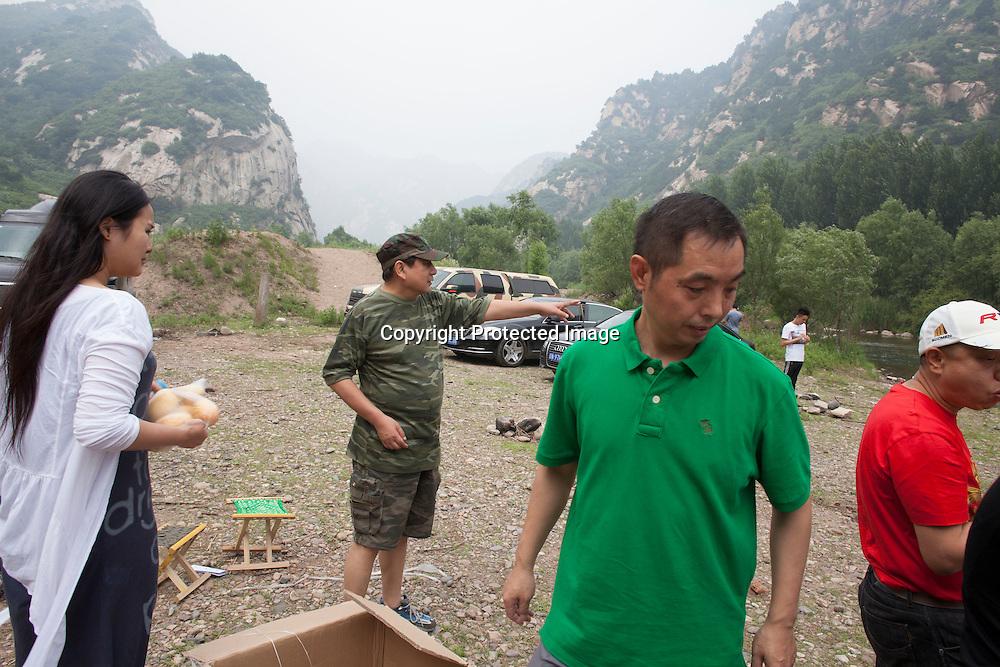 BEIJING, JUNE 24, 2013 : Li Xiaohua kommandiert Mitglieder seines Elite Clubs herum, um sicherzustellen dass bei dem Picknick in Peking's Natur Reservoir Miyun keine Zeit verschwendet wird. Li gruendete den Club vor einem Jahr . Mitglieder koennen nur per Einladung beitreten und muessen ein gewisses Einkommen nachweisen koennen.