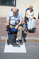 Male wheelchair user using a portable folding travel ramp access a roadside kerb,