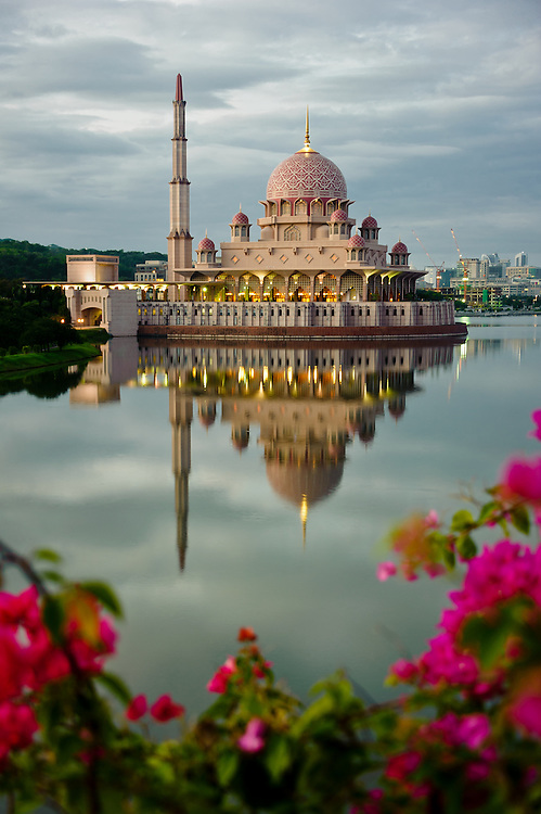 Stock photograph of the Putra Mosque in Putrajaya, Malaysia showing the warm pink tiles. The mosque is reflected in the water of the lake at dawn and framed by pink bougainvillea.