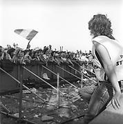 Steward watching crowd standing behind the barrier, Glastonbury, Somerset, 1989