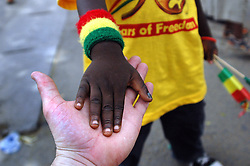 Ghana, Accra, 2007. A Ghanaian child celebrating Independence Day takes the hand of a stranger in friendship.