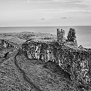 The remains of Dunseverick Castle in county Antrim, Northern Ireland. This is all that remains of a once significant structure. Just to the left is the Giants' Causeway.  The black and white rendering adds to the appearance of aging and decay.