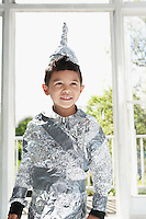 Portrait of young boy (5-6) wearing aluminum foil knight costume indoors