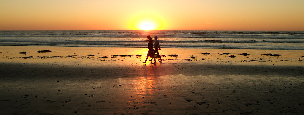 Silhouette of Couple walking along beach in Carlsbad, CA at sunset.