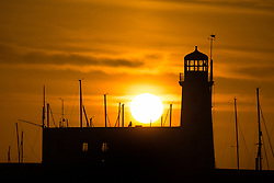 © Licensed to London News Pictures. 13/04/2017. Scarborough UK. The sun rises this morning behind the light house at Scarborough marina in Yorkshire. Photo credit: Andrew McCaren/LNP
