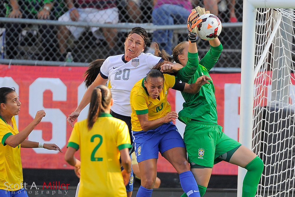U.S. forward Abby Wambach (20) tries to head the ball in the goal as Brazil goalkeeper Luciana, right, gets possession as Brazil midfielder Rosana (10) comes in to help out during the first half of an international friendly soccer match on Nov. 10, 2013 in Orlando, Florida. <br /> <br /> &copy;2013 Scott A. Miller