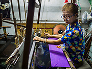 "31 MARCH 2017 - BANGKOK, THAILAND: A woman weaves Thai silk in a home in the Ban Krua neighborhood in Bangkok. The Ban Krua neighborhood of Bangkok is the oldest Muslim community in Bangkok. Ban Krua was originally settled by Cham Muslims from Cambodia and Vietnam who fought on the side of the Thai King Rama I. They were given a royal grant of land east of what was then the Thai capitol at the end of the 18th century in return for their military service. The Cham Muslims were originally weavers and what is known as ""Thai Silk"" was developed by the people in Ban Krua. Several families in the neighborhood still weave in their homes.                    PHOTO BY JACK KURTZ"