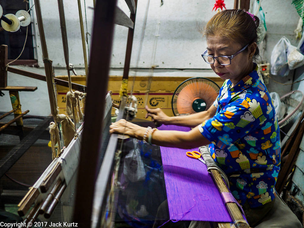 """31 MARCH 2017 - BANGKOK, THAILAND: A woman weaves Thai silk in a home in the Ban Krua neighborhood in Bangkok. The Ban Krua neighborhood of Bangkok is the oldest Muslim community in Bangkok. Ban Krua was originally settled by Cham Muslims from Cambodia and Vietnam who fought on the side of the Thai King Rama I. They were given a royal grant of land east of what was then the Thai capitol at the end of the 18th century in return for their military service. The Cham Muslims were originally weavers and what is known as """"Thai Silk"""" was developed by the people in Ban Krua. Several families in the neighborhood still weave in their homes.                    PHOTO BY JACK KURTZ"""