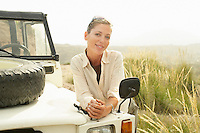 Woman standing by four wheel drive car outdoors portrait
