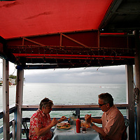 ANNA MARIA ISLAND, FL -- July 9, 2009 -- Ray and Maureen Flock, part-time residents of Anna Maria, eat the grouper sandwich and fish n' chip respectively at Rod & Reel Pier on Anna Maria Island in Manatee County, Fla., on Thursday, July 9, 2009.  (Chip Litherland for The New York Times)