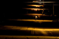 A man walks through a pool of light supplied by an overhead sodium vapor lamp on the main street in Beecher.