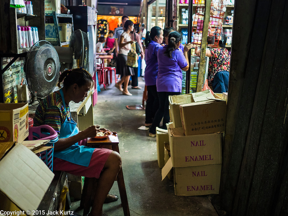 29 SEPTEMBER 2015 - BANGKOK, THAILAND:  A woman eats her lunch in a market near Saphan Lek. Street vendors and illegal market vendors in the Saphan Lek area will be removed in the next two weeks as a part of an urban renewal project coordinated by the Bangkok Metropolitan Administration. About 500 vendors along Damrongsathit Bridge, popularly known as Saphan Lek, have 15 days to relocate. Vendors who don't move will be evicted. Saphan Lek is just one of several markets and street vending areas being closed in Bangkok this year. The market is known for toy and replica guns, bootleg and pirated DVDs and CDs and electronic toys.   PHOTO BY JACK KURTZ