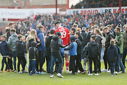 Barnsley fanssurround Barnsley forward Kieffer Moore (19) at full time during the EFL Sky Bet League 1 match between Barnsley and Blackpool at Oakwell, Barnsley, England on 27 April 2019.