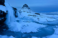 The waterfall Kirkjufellsfoss with icicles and the mountain Kirkjufell at dusk in the winter, village Grundarfjoerdur, Peninsula Snaefellsnes, Iceland