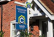 Estate agent sold sign outside modern house, Melton, Suffolk, England, UK