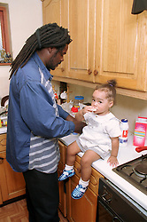 Father preparing food in kitchen with young daughter sitting on work surface,