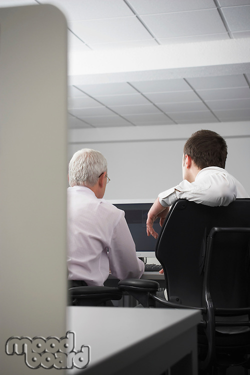 Two businessmen using computer in office cubicle back view